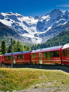Train of Rhaetian Railway, Bernina Express, in the area of Bernina Massif and Glacier Morteratsch.