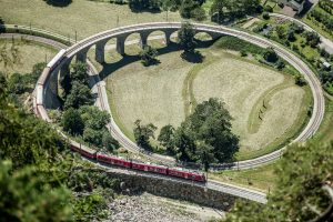 Bernina Express train on the round viaduct in Brusio.
