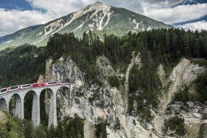 Pociąg Glacier Express na wiadukcie Albula wjeżdża do tunelu w masywie górskim.