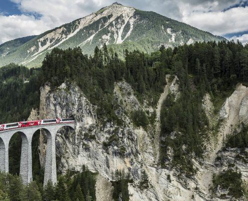 Glacier Express train on the viaduct of Albula enters the tunnel in the mountain massif.