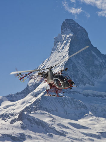 Helicopter in flight, Matterhorn mountain in the background.